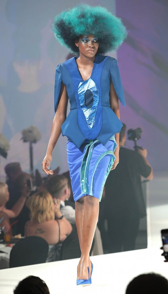 woman with blue curly hair on a catwalk